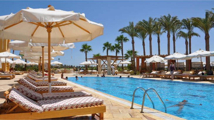 Sun loungers and parasols by the pool at a luxury hotel - cheap hotel booking tips featured image